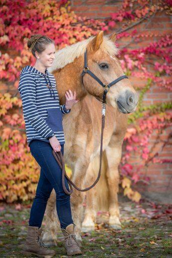 Reiterin und Pferd vor Mauerwerk mit buntem Herbstlaub in Szene gesetzt