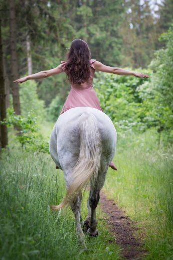 Wie bei Pipi Langstrumpf: Reiterin sitz mit seitlich ausgestreckten Armen auf ihrem Schimmel
