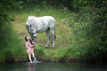 Ein Foto wie aus einem Märchen: Junge Reiterin hockt am See und planscht mit den Füßen im Wasser, das Pferd steht hinter ihr
