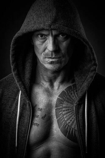 Dunkles Studiofoto eines ernst blickenden Kampfsportlers