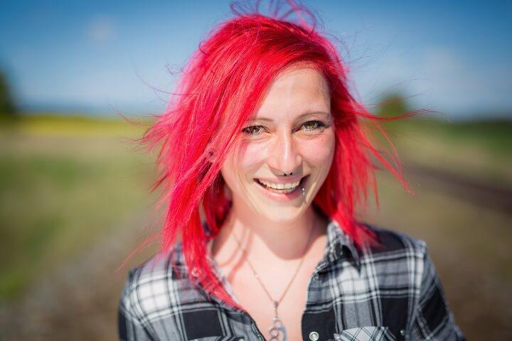 Porträt einer rothaarigen jungen Frau mit Piercings