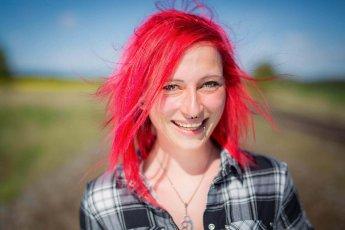 Portraitaufnahme einer fröhlichen jungen Frau mit feuerroten Haaren und Piercings