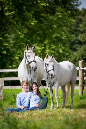 Junges Liebespaar sitzt im Gras und ist an zwei stehende Pferde angelehnt