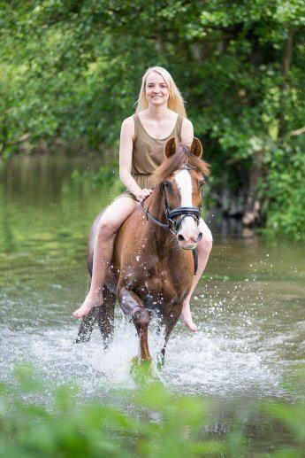 Reiterin mit ihrem Pferd im flachen See. Für die Kamera wurde das Wasser ordentlich spritzen gelassen