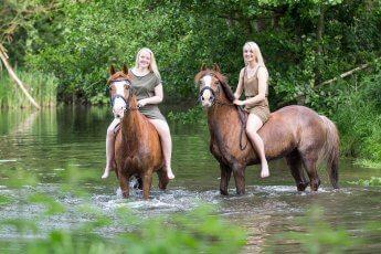 Sommerliches Fotoshooting mit zwei Pferden, die mit ihren Reiterinnen auf dem Rücken in einem Teich stehen