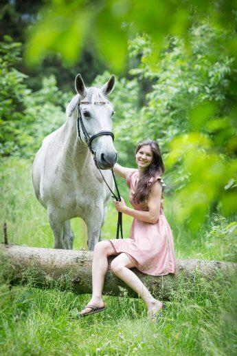 Während unscharf Blätter ins Foto ragen, sitzt im Hintergrund die Reiterin auf einem umgestürzten baum und hält ihr Pferd am Zügel
