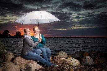 Zwei Schwestern unter weißem Schirm im Sonnenuntergang an der Ostsee