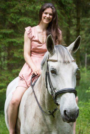Reiterin lächelt auf einem Schimmel sitzend in die Kamera