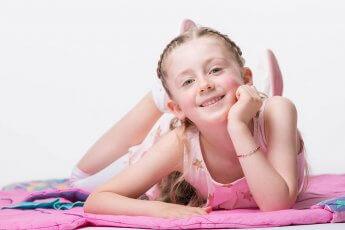 Kleines Mädchen auf ihrer Spieldecke liegend im Fotostudio vor weißem Hintergrund