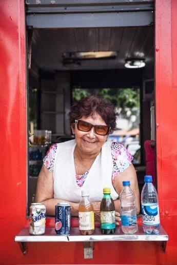 Brasilianische Getränkeverkäuferin blickt lächelnd aus ihrem Verkaufsstand in die Linse