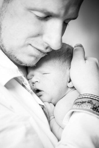 Im richtigen Moment auf den Auslöser gedrückt: der junge Vater hält behutsam seinen Sohn auf dem Arm