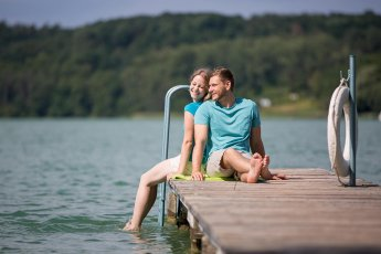 Liebespaar Rücken an Rücken gelehnt auf einem Badesteg