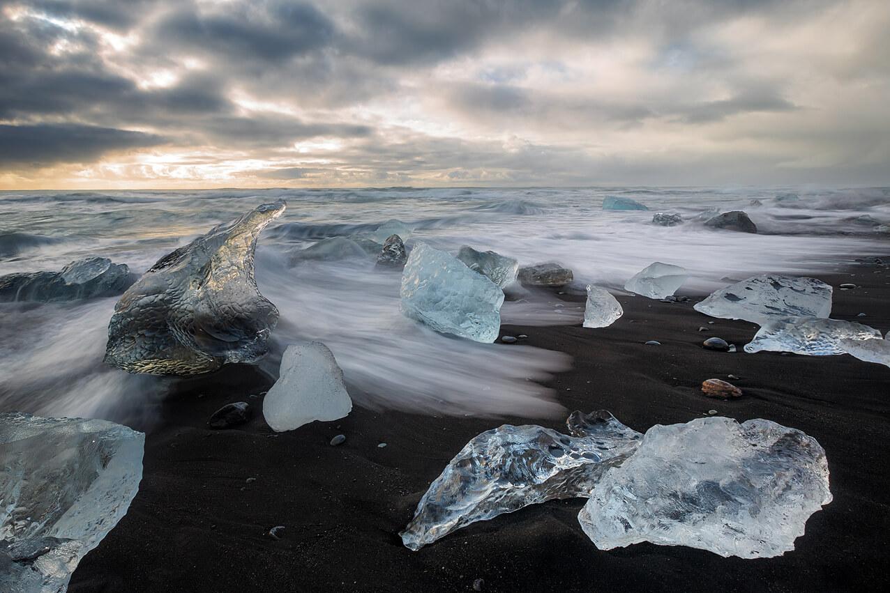 Langzeitbelichtung am schwarzen Lavastrand mit Eisblocken auf Island