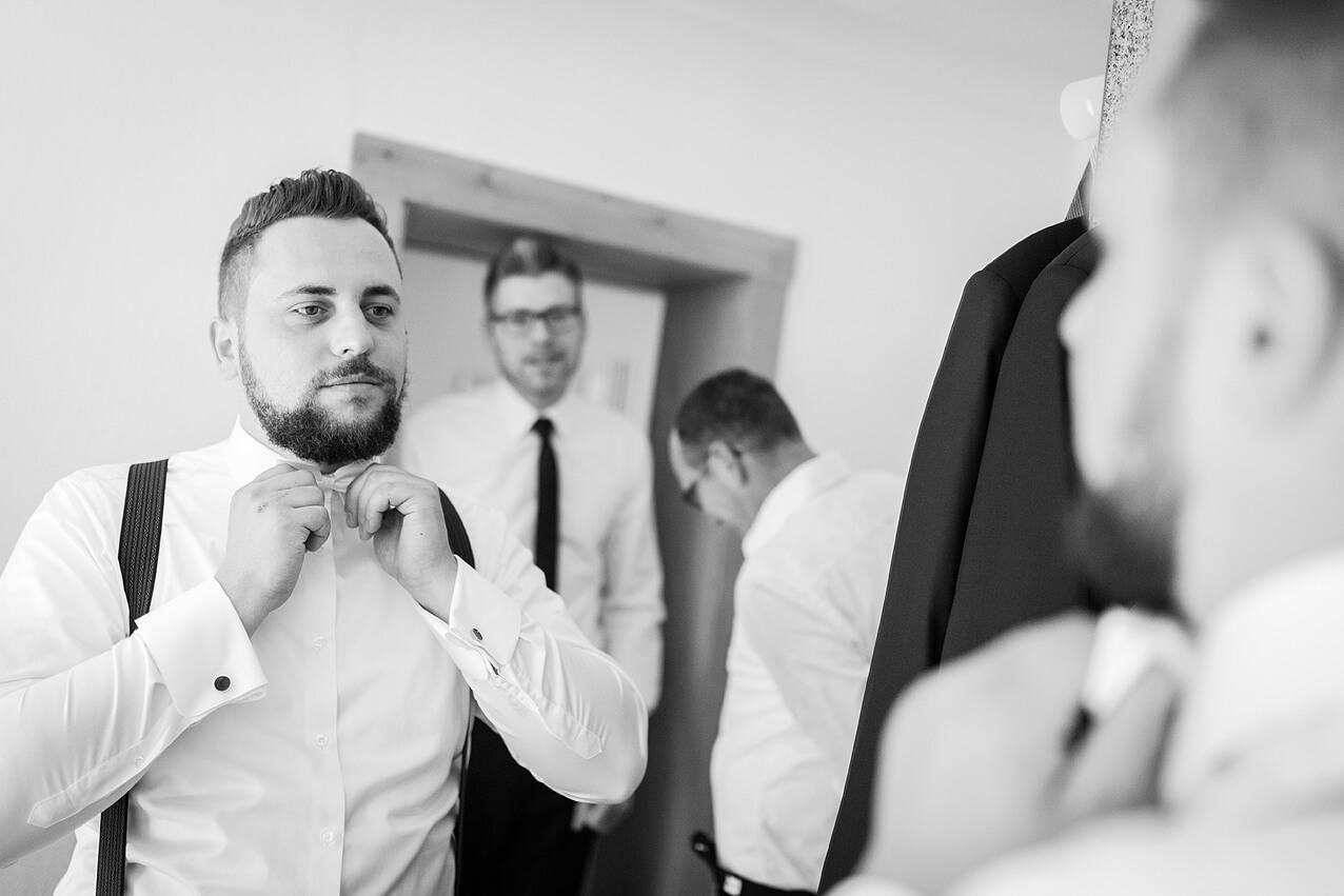 Der Bräutigam bindet sich die Fliege vor dem Spiegel