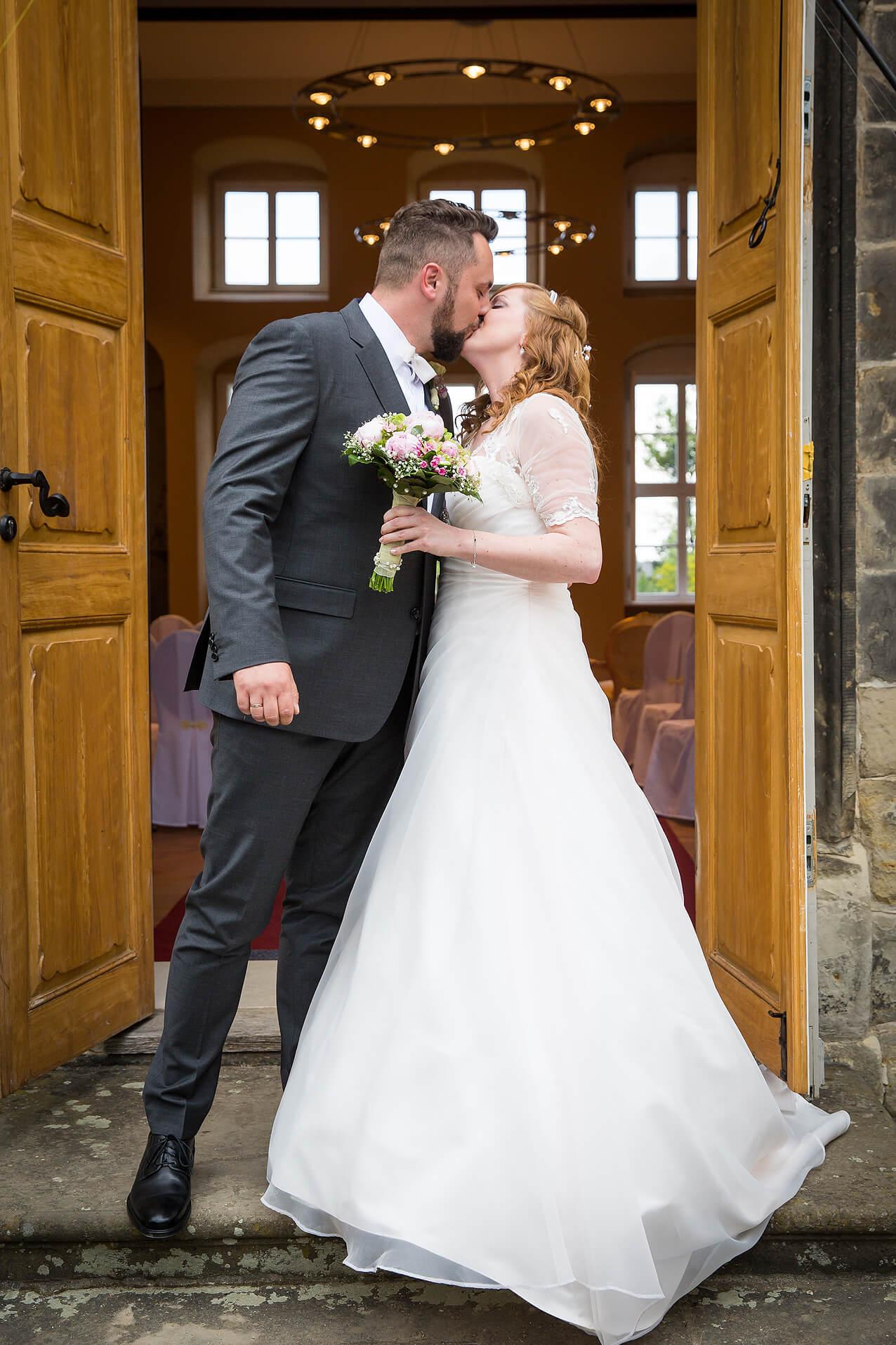 Das Brautpaar küsst sich vor dem Standesamt