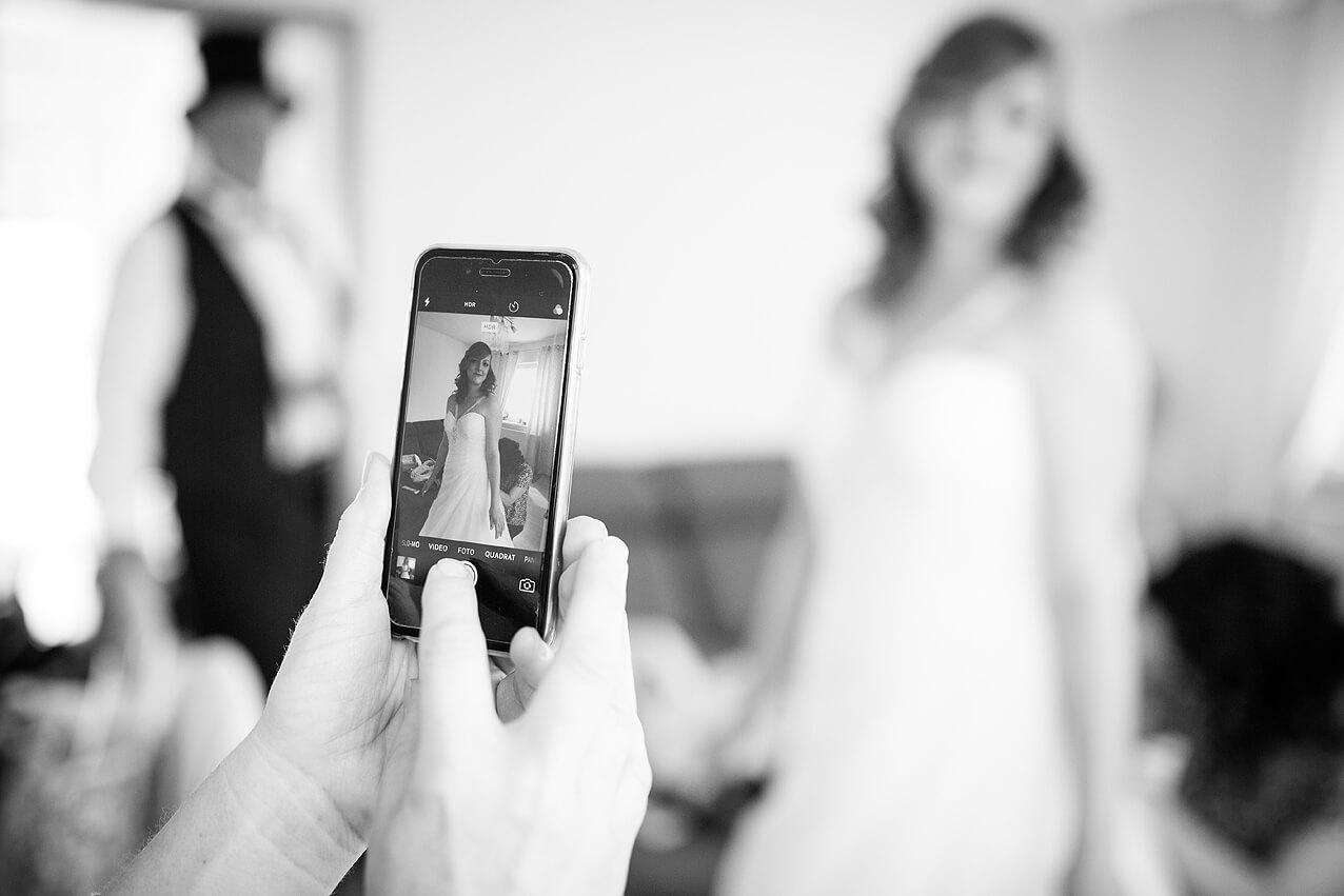Das Brautkleid samt Braut auf dem Handy