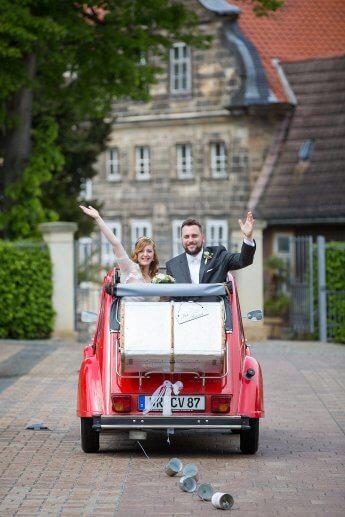 Brautpaar im Hochzeitswagen – eine rote Ente