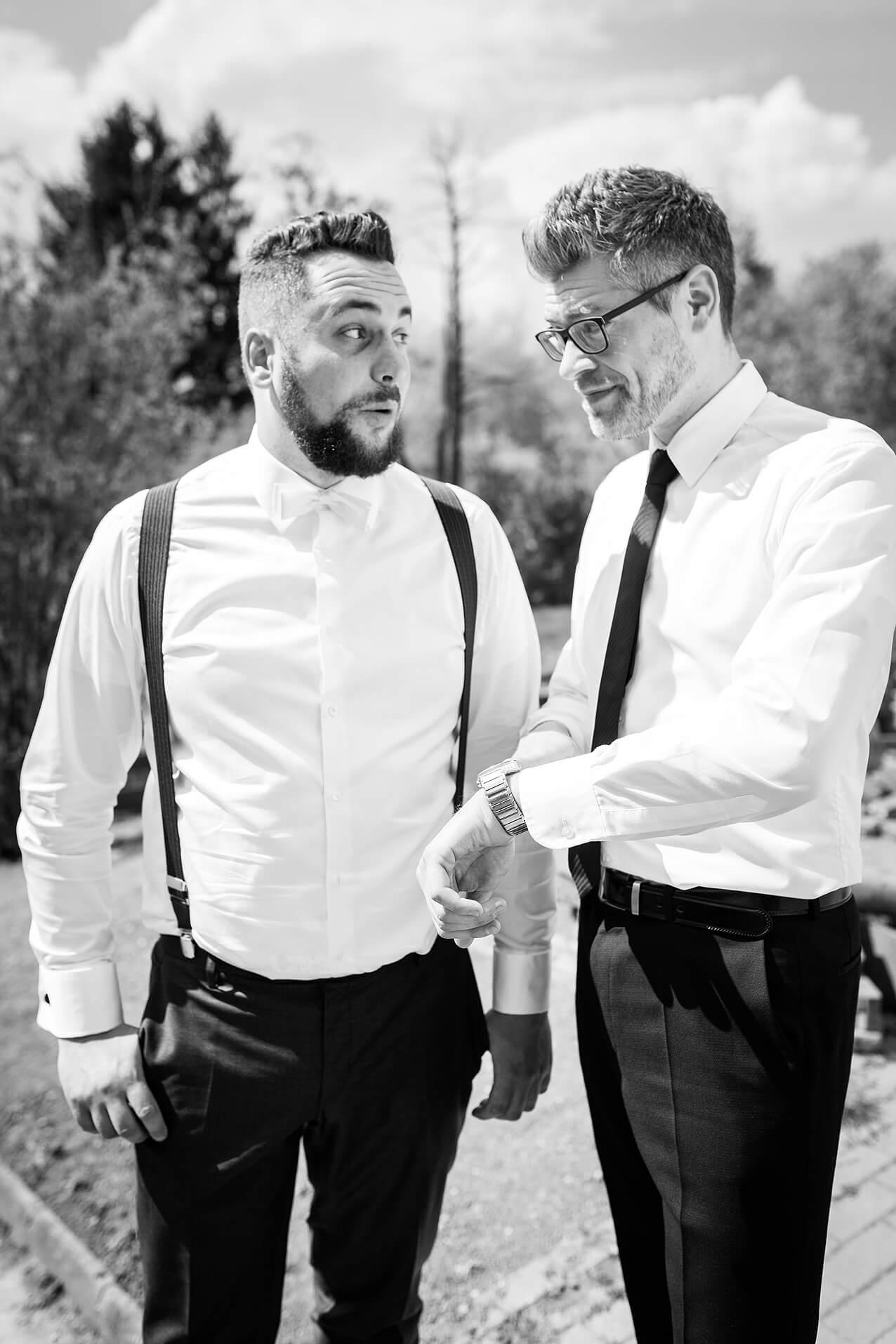 Bräutigam und Trauzeuge blicken während der letzten Hochzeitsvorbereitungen auf die Uhr