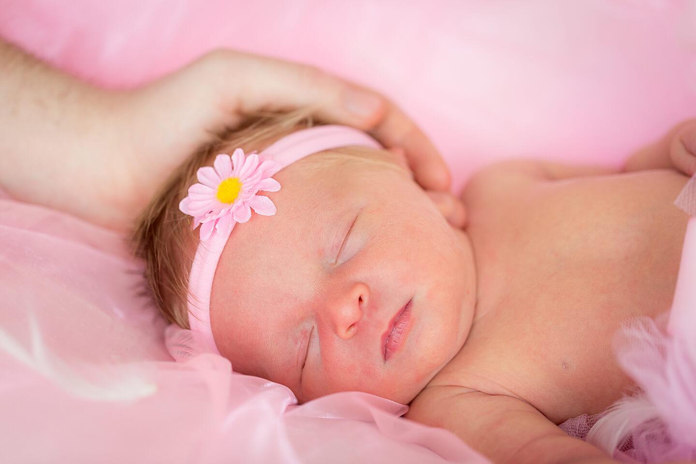 Schlafendes Neugeborenes mit der schützenden Hand das Vaters am Köpfchen