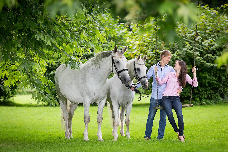 Junges Paar auf der Schaukel beim Fotoshooting mit zwei Pferden