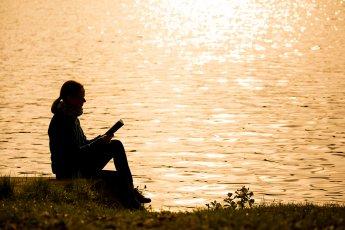 Junge Frau im warmen Gegenlicht beim Lesen eines Buches am See