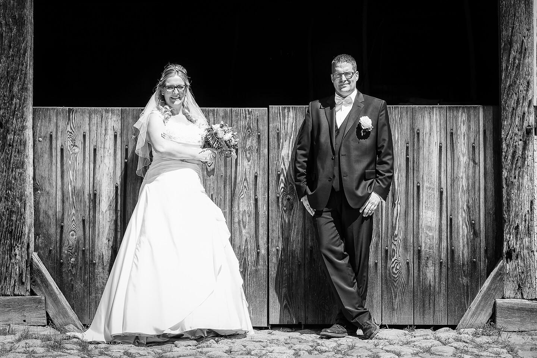 Hochzeitsfoto in schwarzweiss vor Scheunentor