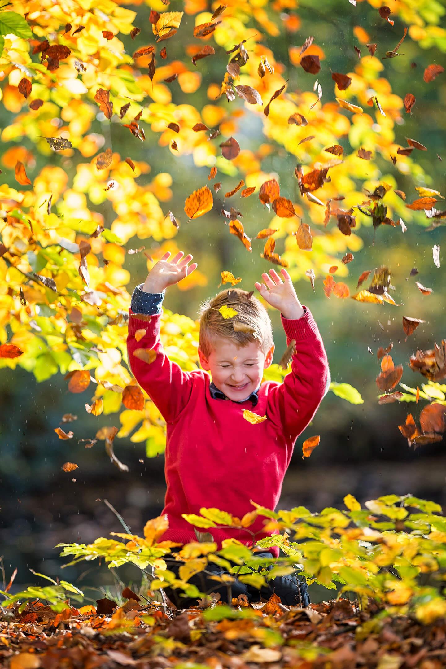 Herbstliches Kinderfoto mit fliegendem Laub