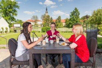 Unternehmensfotografie – Drei junge Damen trinken Kaffee auf der Terrasse eines Restaurants