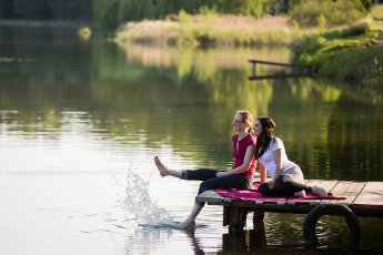 Zwei junge Frauen sitzen auf einem Steg am See