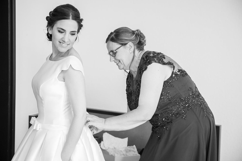 Brautmutter schnürt das Brautkleid