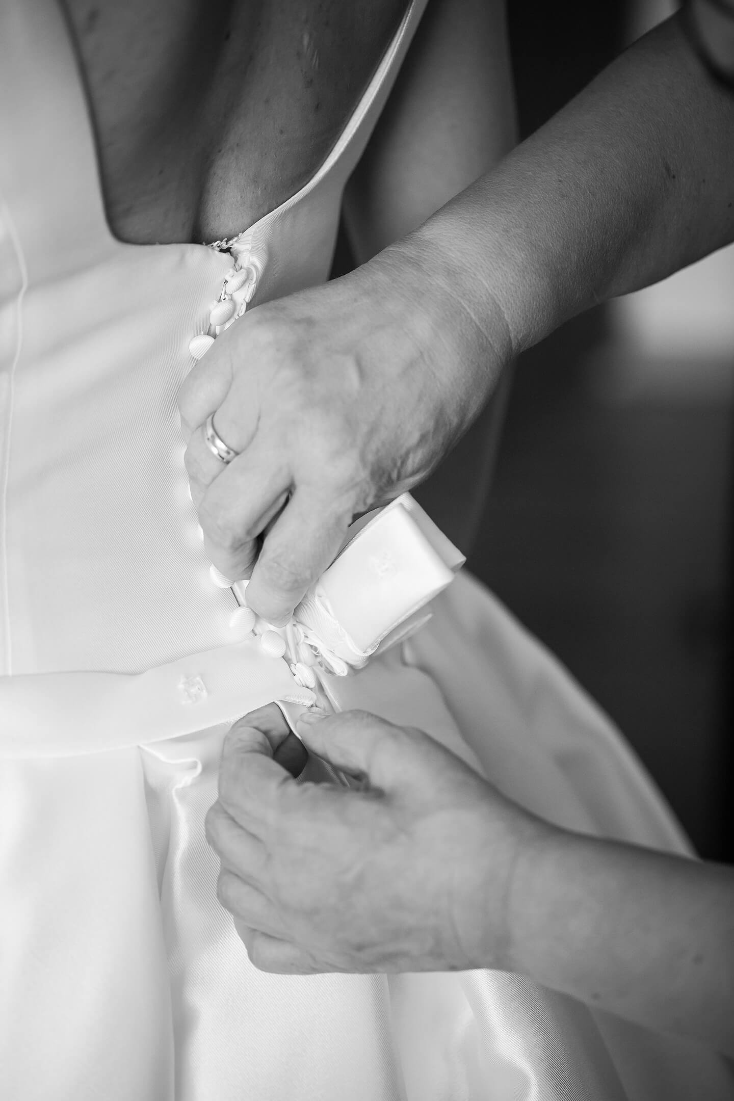 Detailfoto vom Schnueren des Brautkleids