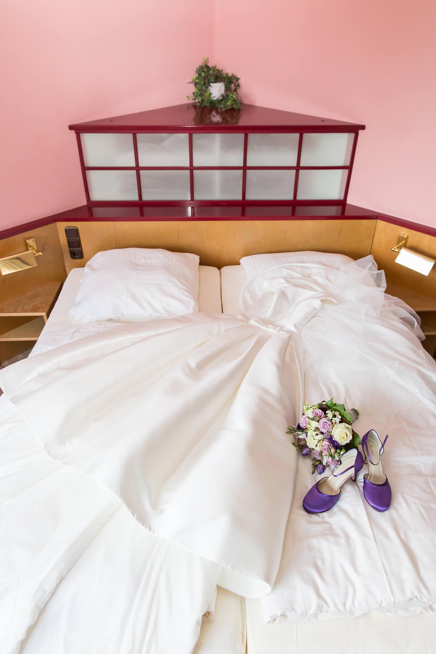 Brautkleid und Brautstrauss auf dem Hotelbett im Hotel Holst