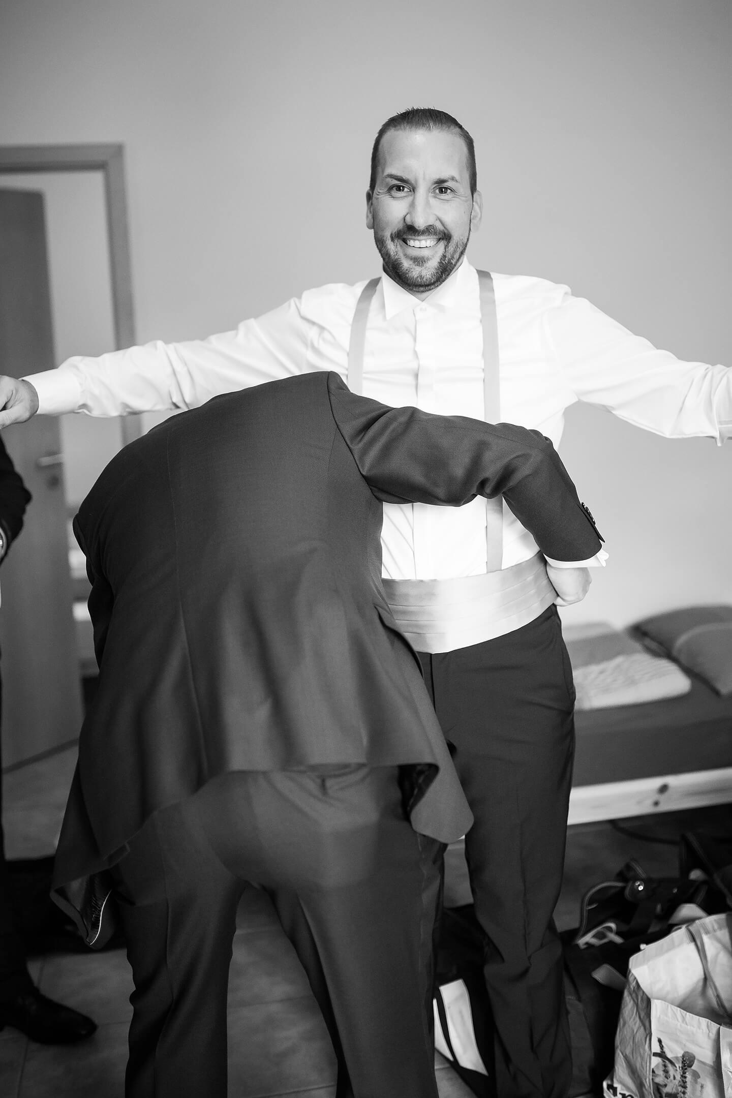 Bräutigam lässt sich bei der Ankleide helfen