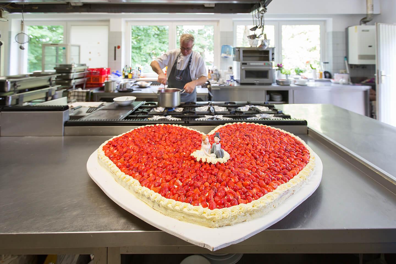 Große Erdbeer-Hochzeitstorte in der Küche der Hochzeitslocation Westerhof