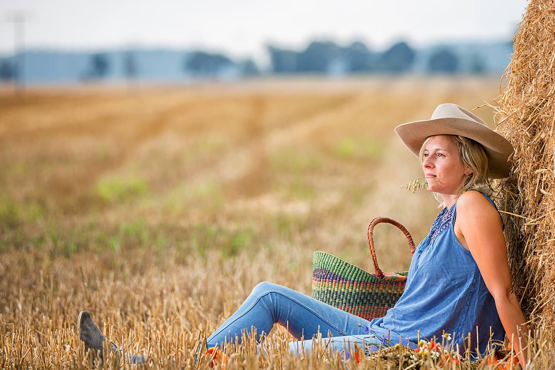 Portraitshooting auf einem Feld mit junger Frau in Jeanskleidung und Cowboy-Hut