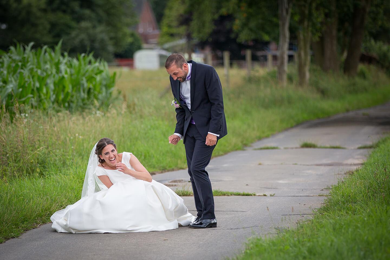 Hochzeitspaar beim Fotoshooting eine Sekunde nachdem das Brautkleid zerriss