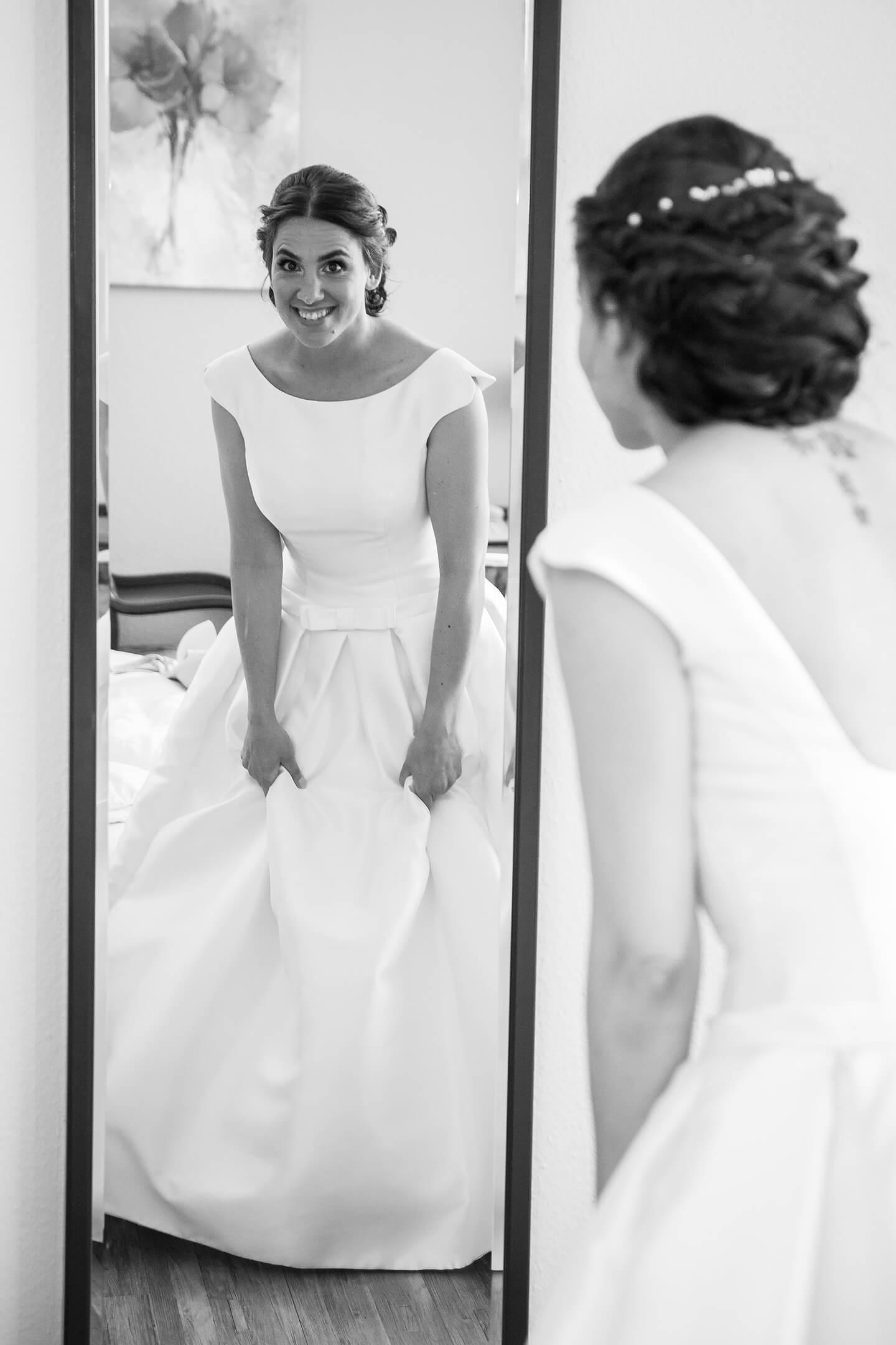 Braut im Hochzeitskleid schaut in den Spiegel
