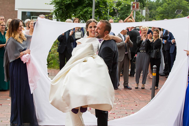 Bräutigam trägt Braut durchs ausgeschnittene Herz