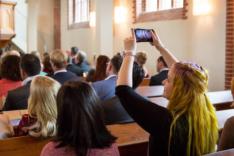 Während der Trauung wird ein Foto mit dem Smartphone gemacht