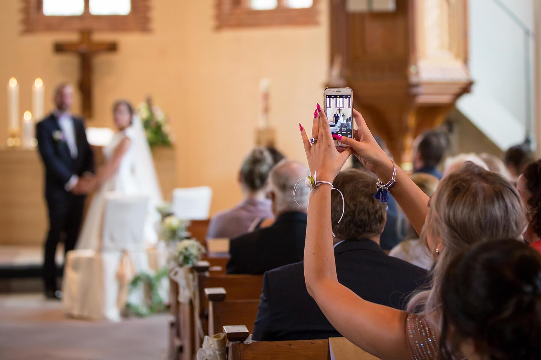 Gast macht Handyfoto von der Trauung in der St Paulus Kirche