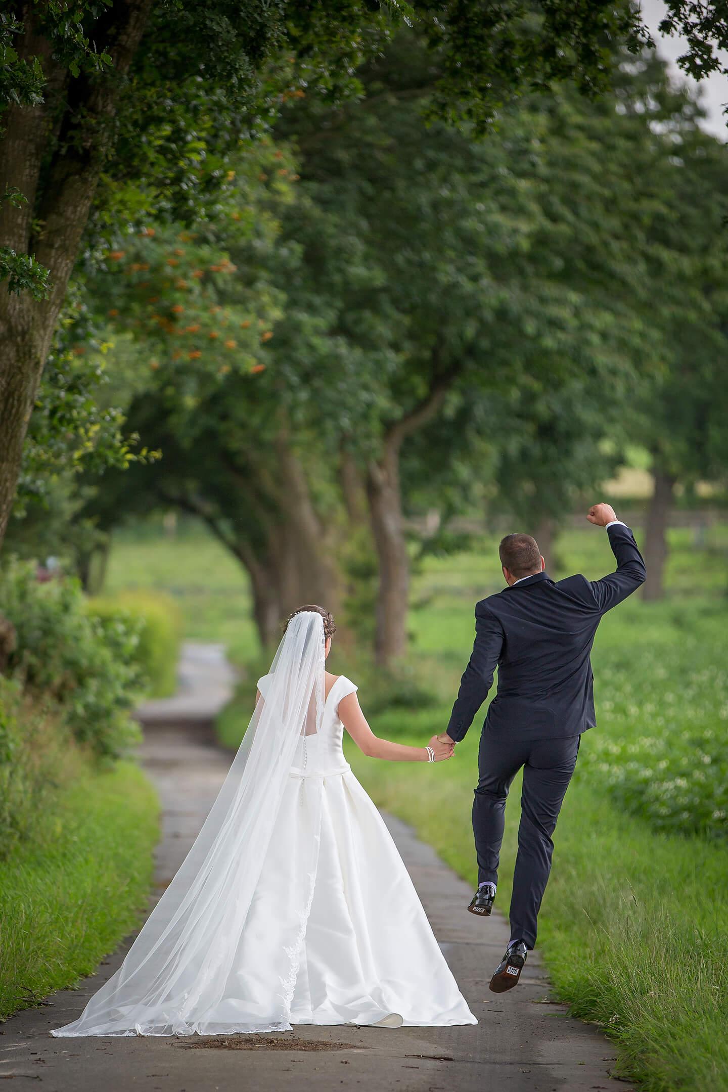 Brautpaar von hinten fotografiert und der Bräutigam springt vor Freude in die Luft