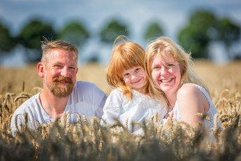 Junge Familie beim Fotoshooting im sommerlichen Kornfeld
