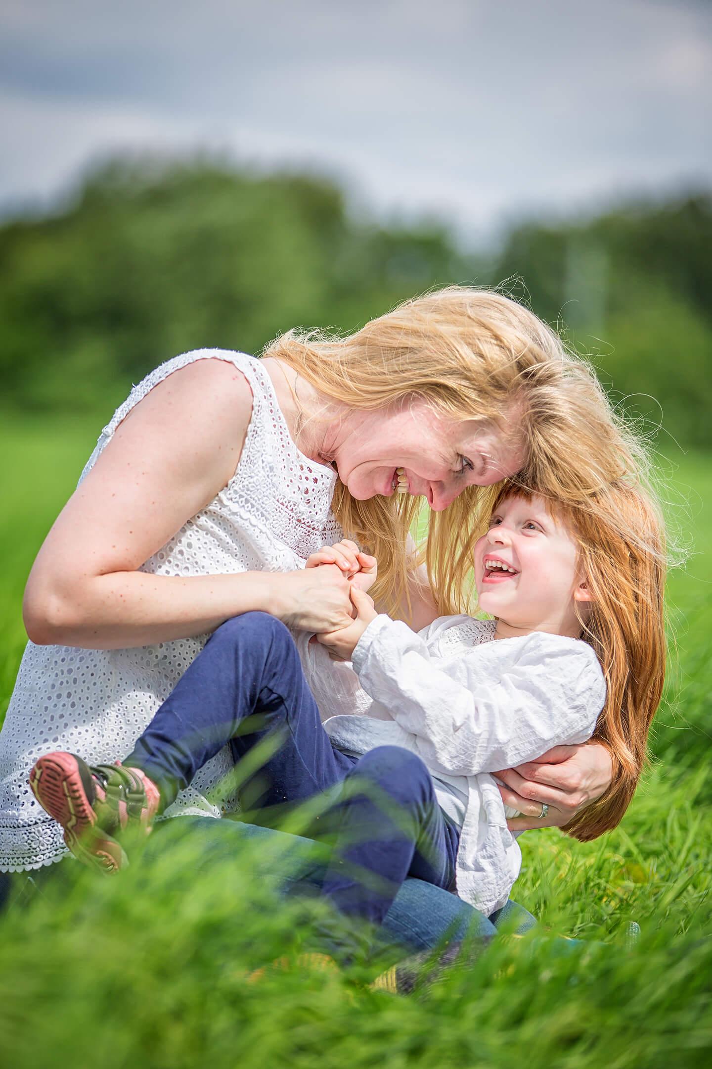 Mama und Tochter tollen miteinander beim Familienshooting im Grünen