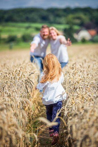 Familienfoto im Kornfeld: Tochter rennt in die Arme der Eltern