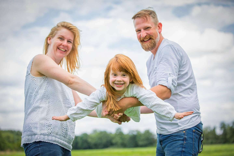 Beim Familienshooting: Tochter spielt Flieger auf den Armen der Eltern