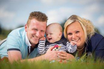 Glückliches Ehepaar mit Baby auf der Wiese liegend