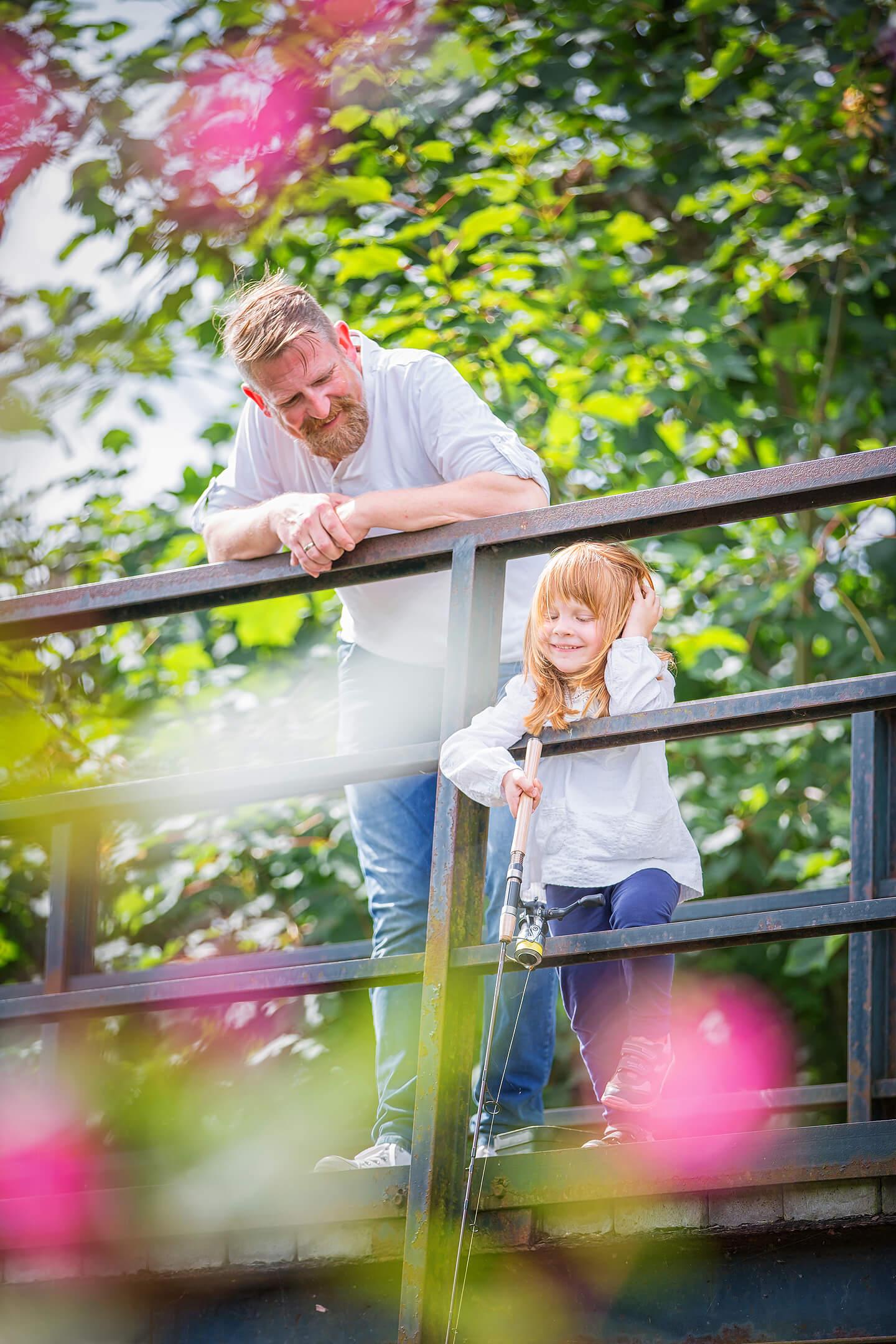 Papa und Tochter angeln auf einer kleinen Brücke