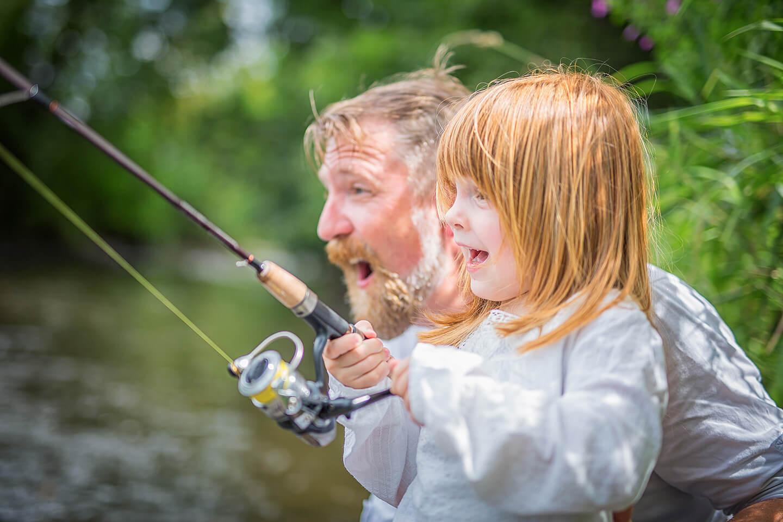 Papa und Tochter beim Angeln mit aufgeregten Gesichtern