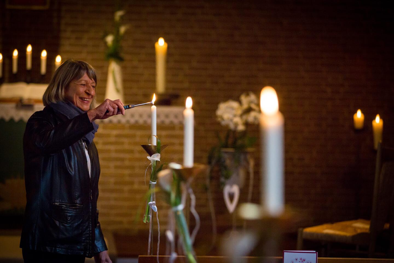 Küsterin zündet die Kerzen vor der kirchlichen Trauung an