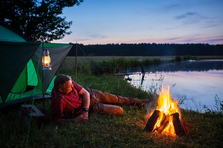 Angler am Lagerfeuer kurz nach Sonnenuntergang